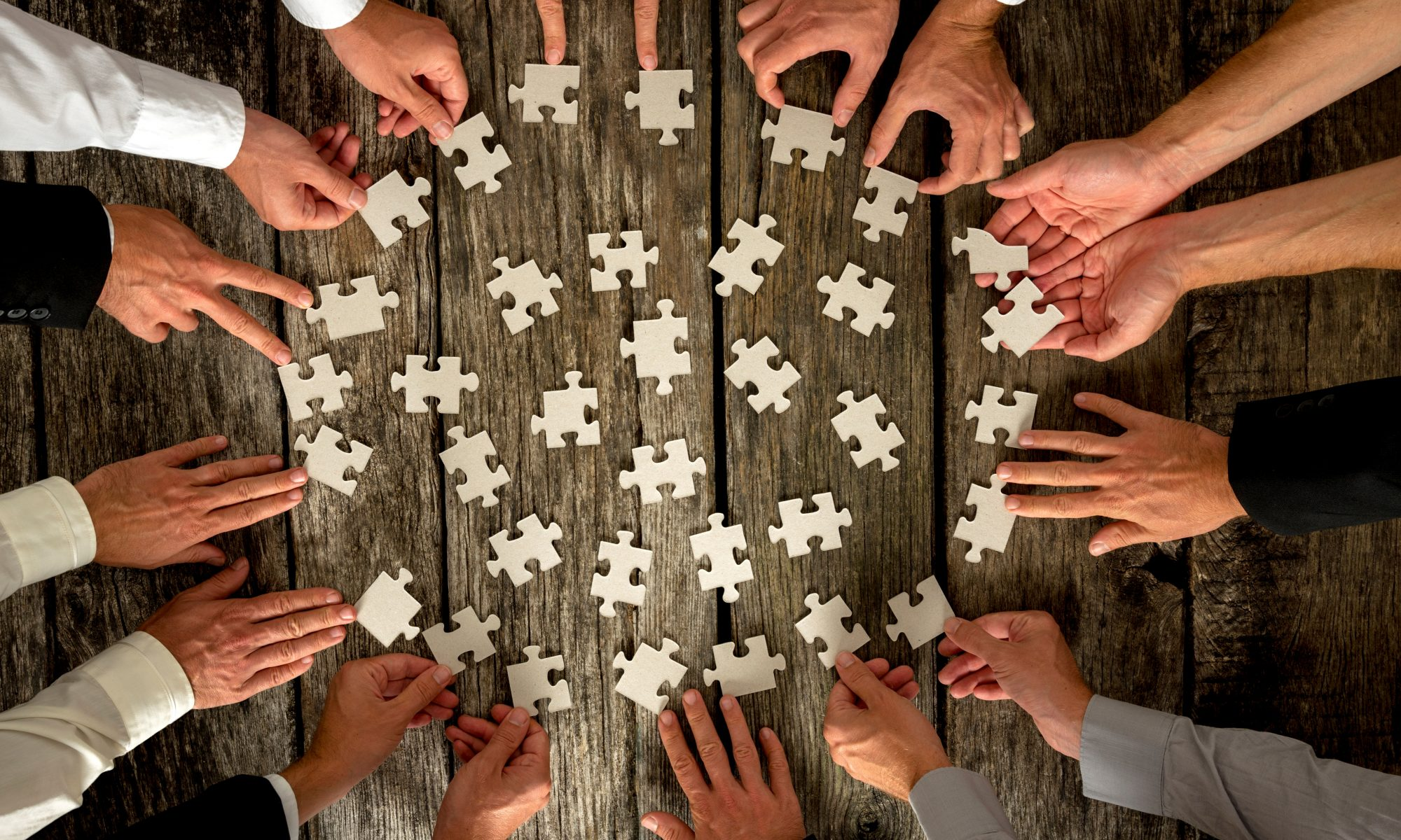 Hands with puzzle pieces for team building