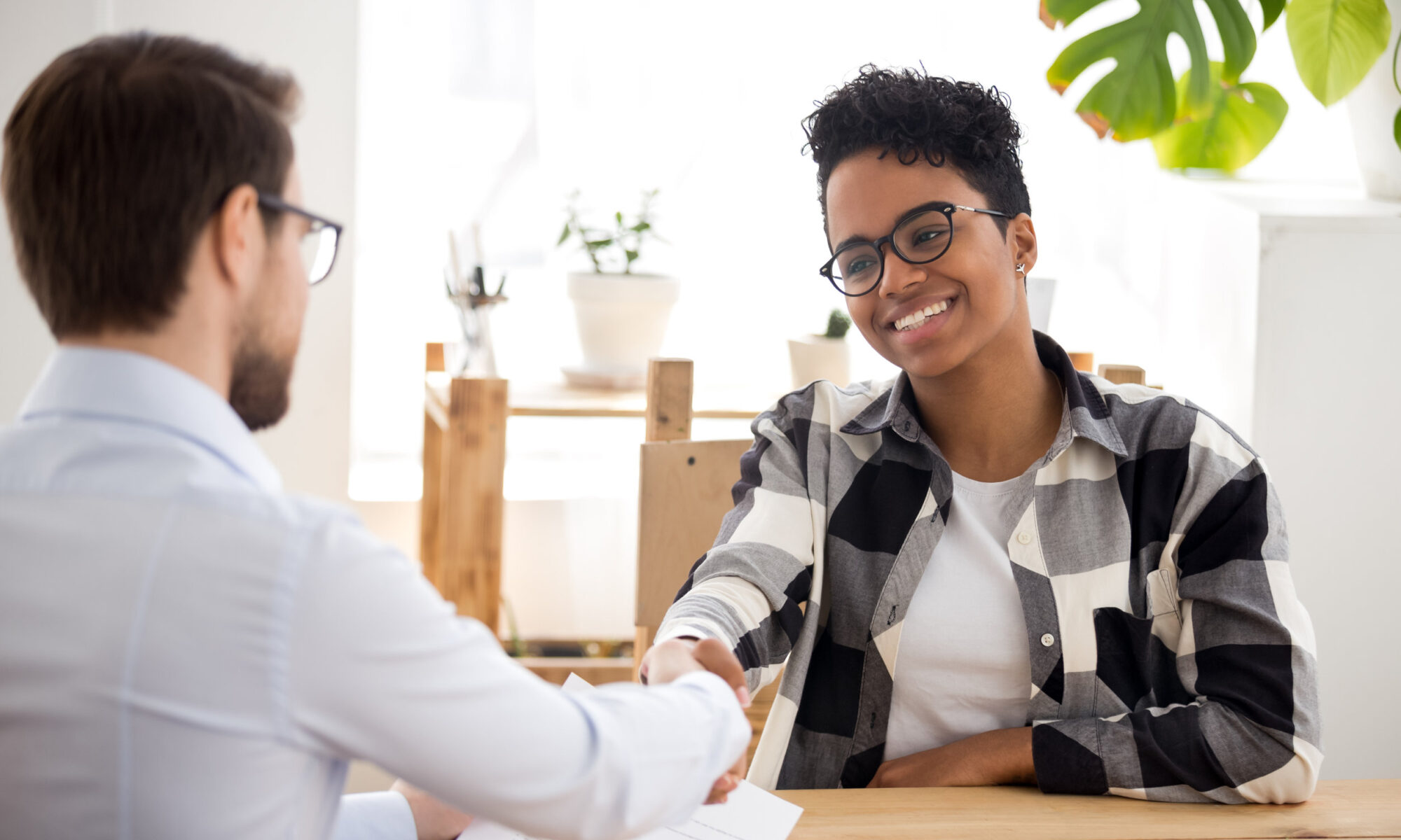 Happy confident applicant shaking hand of hr getting hired